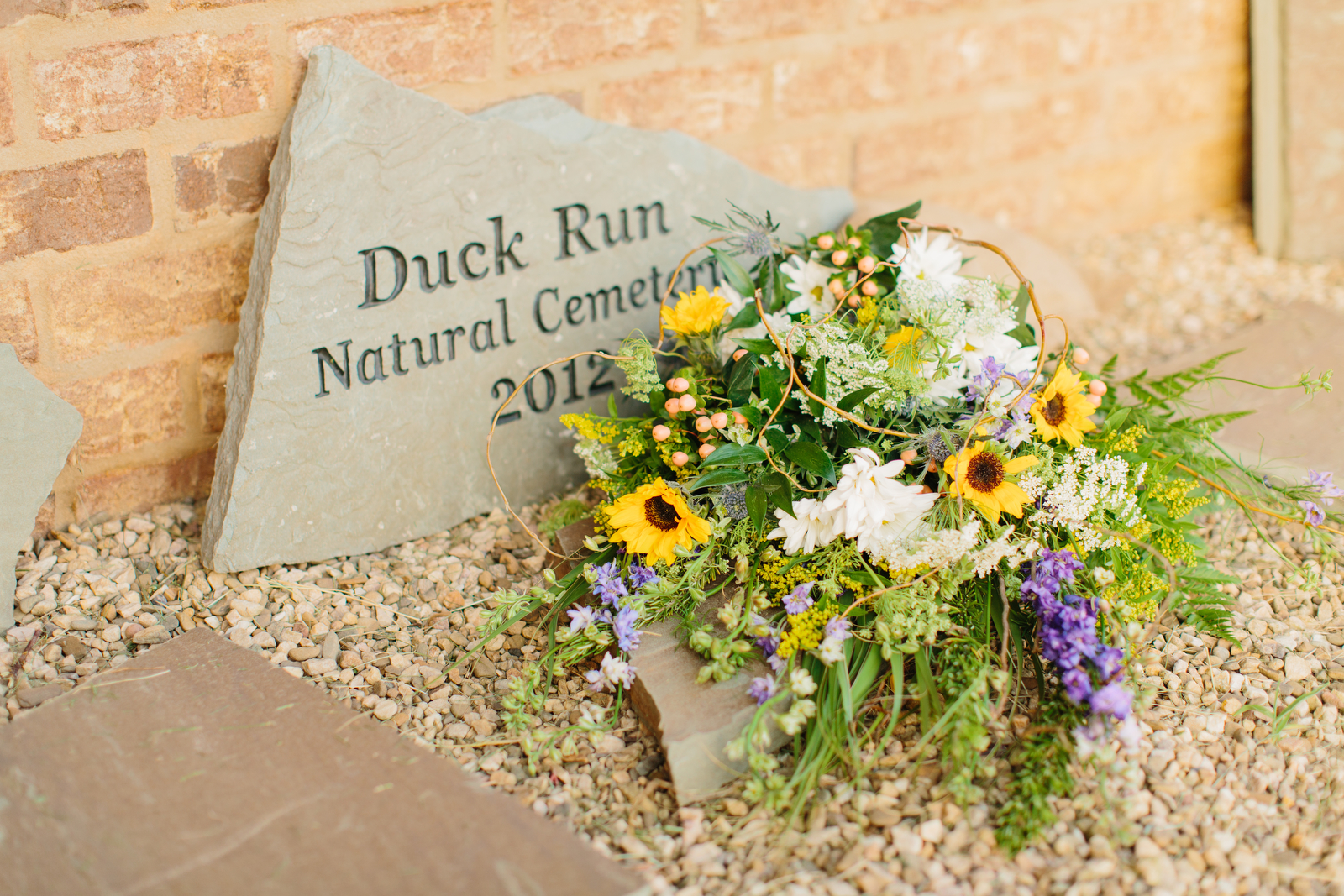 Photograph of flowers at the foot of a slab of stone that is engraved with the words Duck Run Natural Cemetery 2012